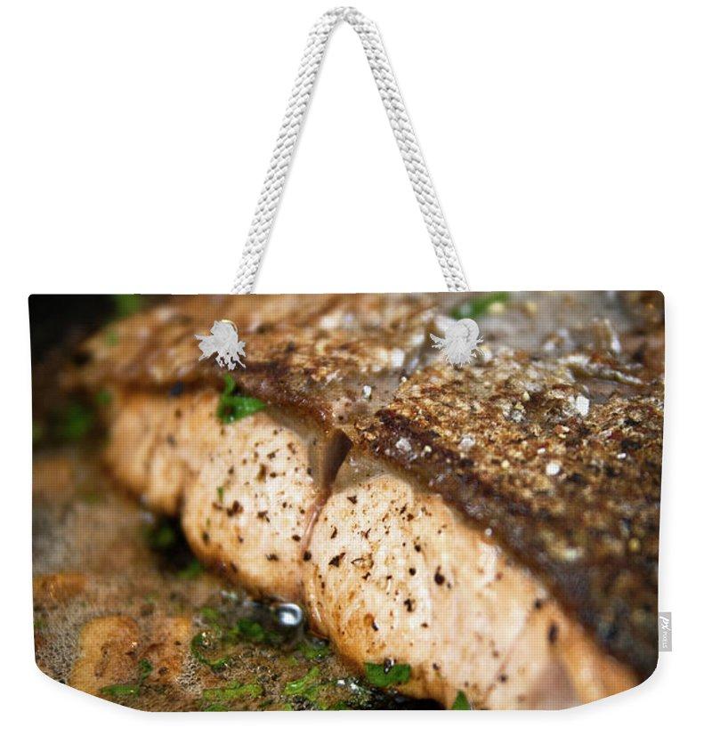 Garlic Weekender Tote Bag featuring the photograph Frying Salmon On Pan by Wojciech Wisniewski
