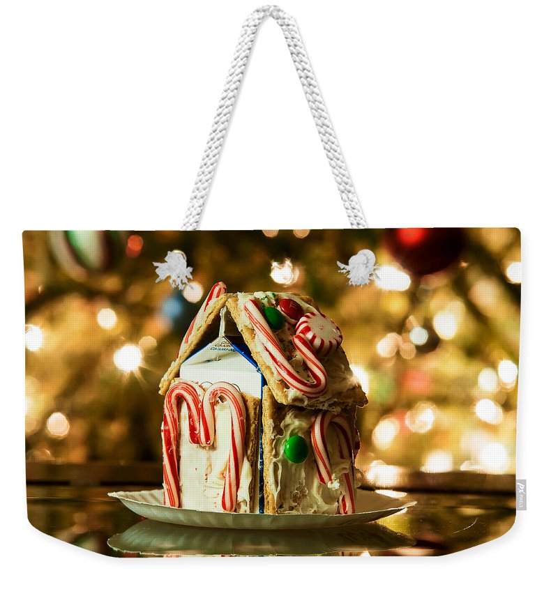 Cute Weekender Tote Bag featuring the photograph Gingerbread House Against A Background Of Christmas Tree Lights by Alex Grichenko