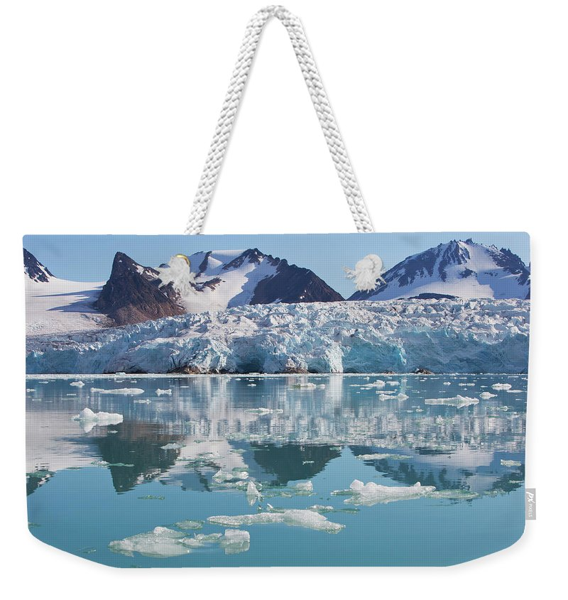 Scenics Weekender Tote Bag featuring the photograph Glaciers Tumble Into The Sea In The by Anna Henly