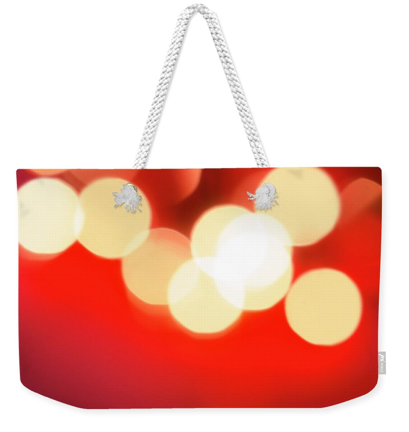 Christmas Lights Weekender Tote Bag featuring the photograph Glowing Light On Red Background, Studio by Tetra Images