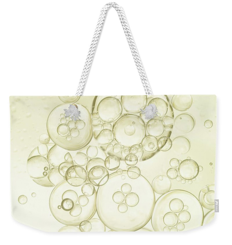 Purity Weekender Tote Bag featuring the photograph Gold Bubbles Of Oil And Water by Level1studio