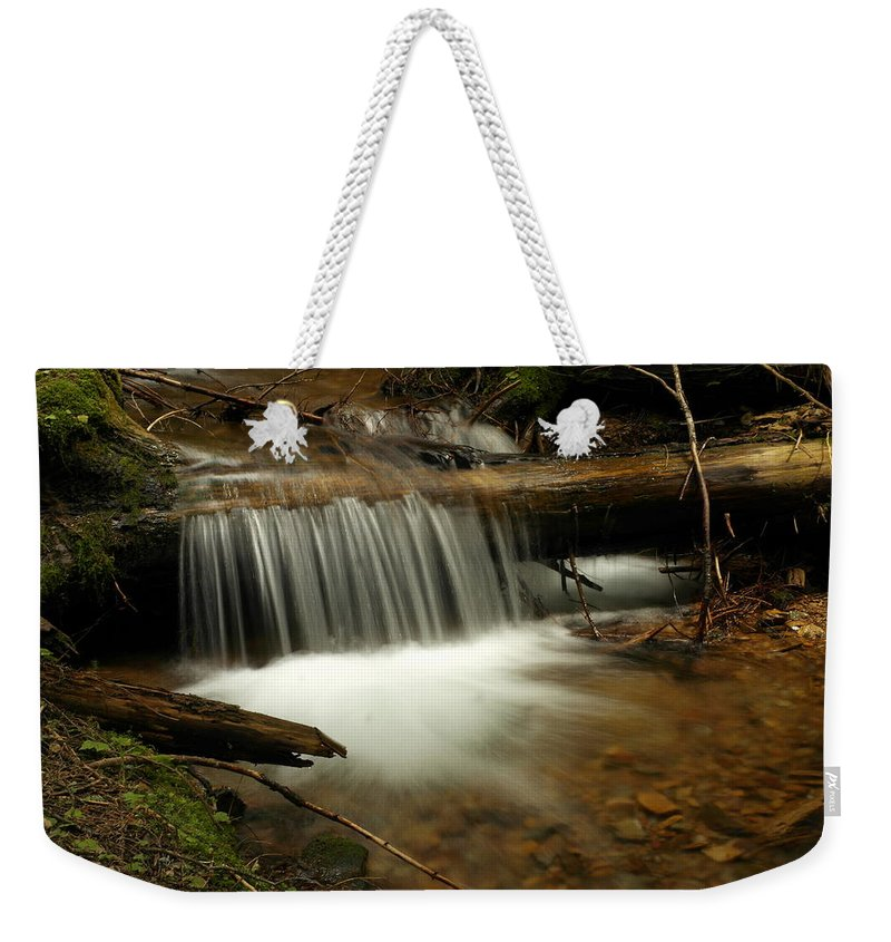 Water Weekender Tote Bag featuring the photograph Gurgling Over A Small Log by Jeff Swan