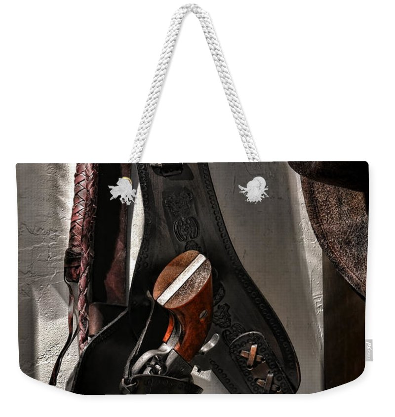 Gun Weekender Tote Bag featuring the photograph Hanging Revolver by Olivier Le Queinec