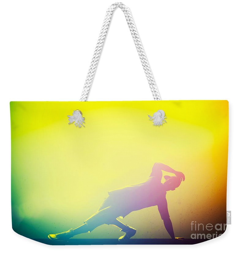 Music Weekender Tote Bag featuring the photograph Hip Hop Break Dance Performed By Young Man In Colorful Club Lights by Michal Bednarek
