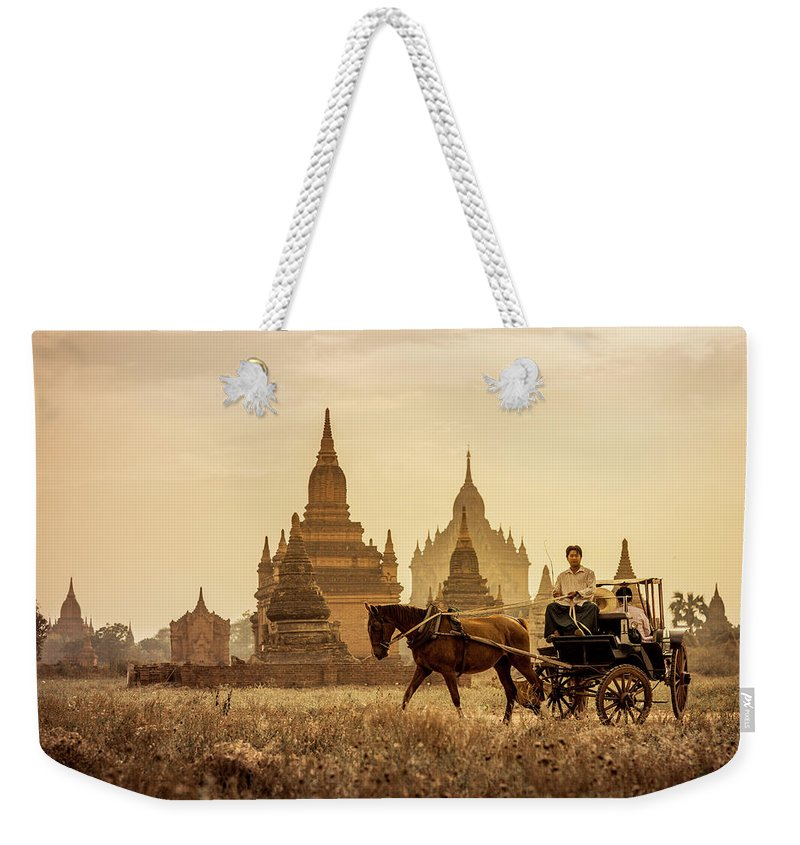 Horse Weekender Tote Bag featuring the photograph Horse And Carriage Turning By Temples by Merten Snijders