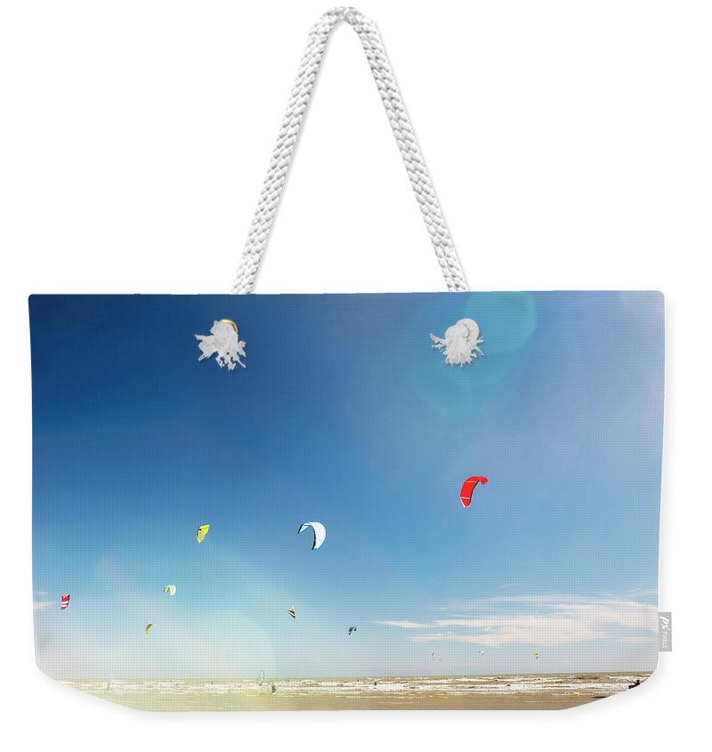 Water's Edge Weekender Tote Bag featuring the photograph Kite Surfers by Nick David