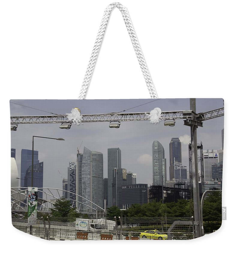 Action Weekender Tote Bag featuring the photograph Lighting Work For The Singapore Formula One And A View Of The Helix Bridge by Ashish Agarwal