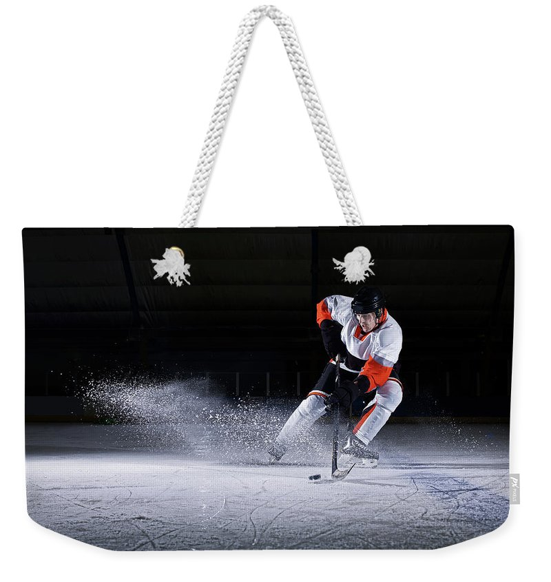 Focus Weekender Tote Bag featuring the photograph Male Ice Hockey Player Taking Puck by Mike Harrington