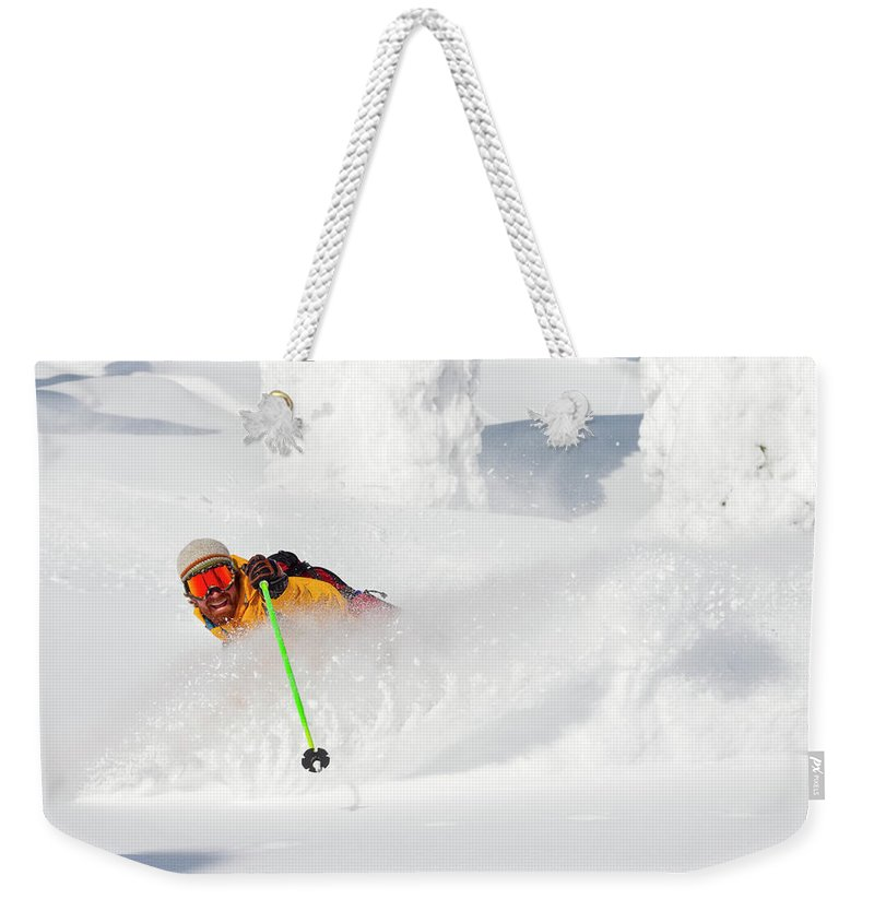 Holding Weekender Tote Bag featuring the photograph Male Skier Makes A Deep Powder Turn by Craig Moore