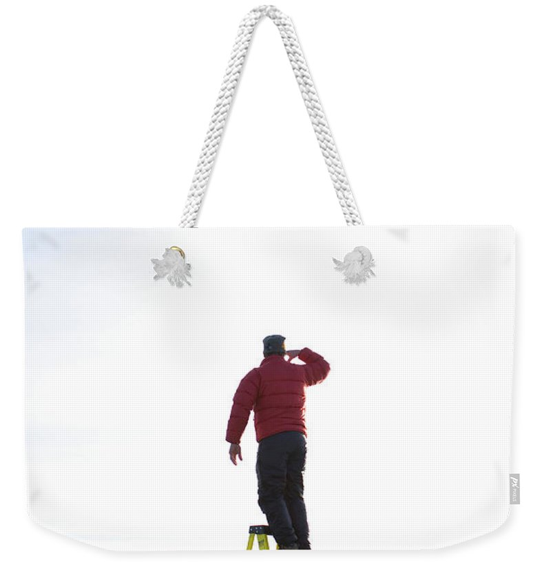 Arm Raised Weekender Tote Bag featuring the photograph Man Atop Ladder On A Frozen Lake by Woods Wheatcroft