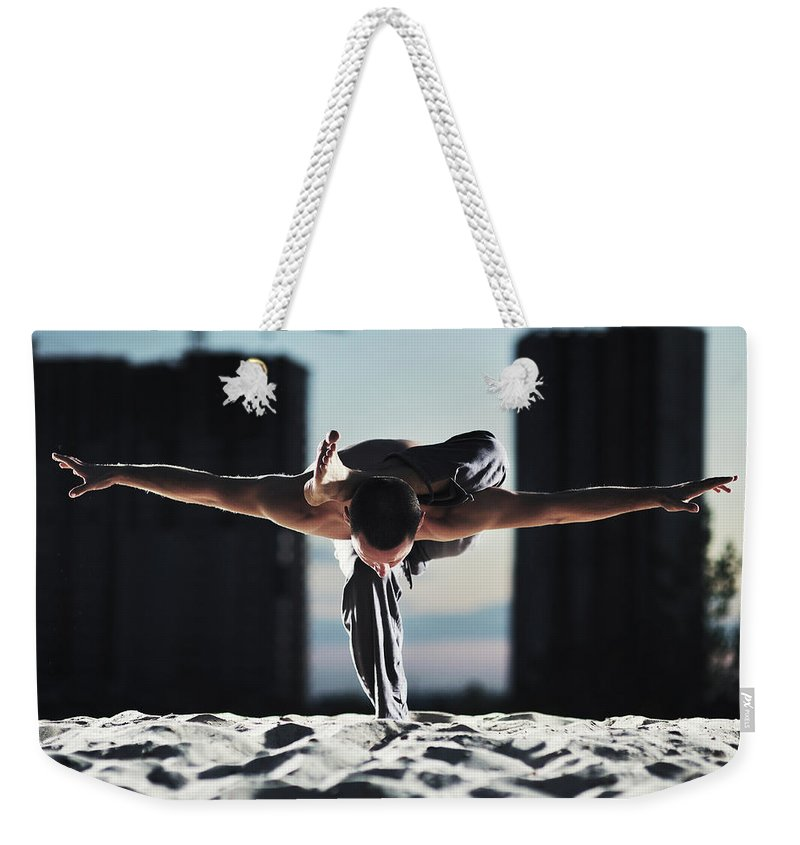 People Weekender Tote Bag featuring the photograph Man Holding Yoga Pose In The Sand by Myshkovsky