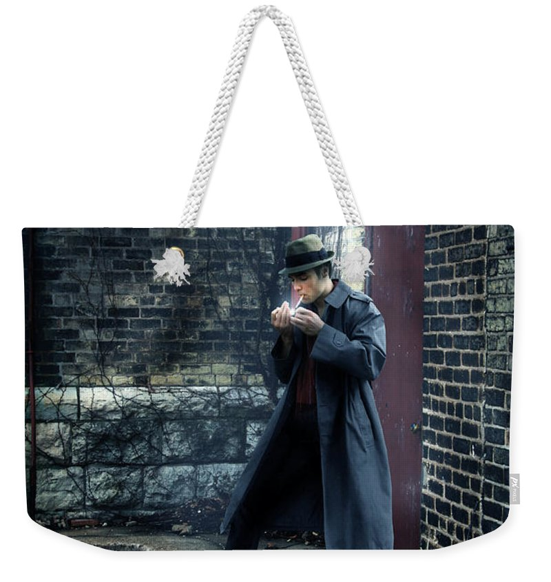 Man Weekender Tote Bag featuring the photograph Man In Trenchcoat Lighting A Cigarette by Jill Battaglia