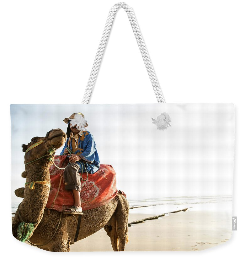 Agadir Weekender Tote Bag featuring the photograph Man On Camel On Beach, Taghazout by Tim E White