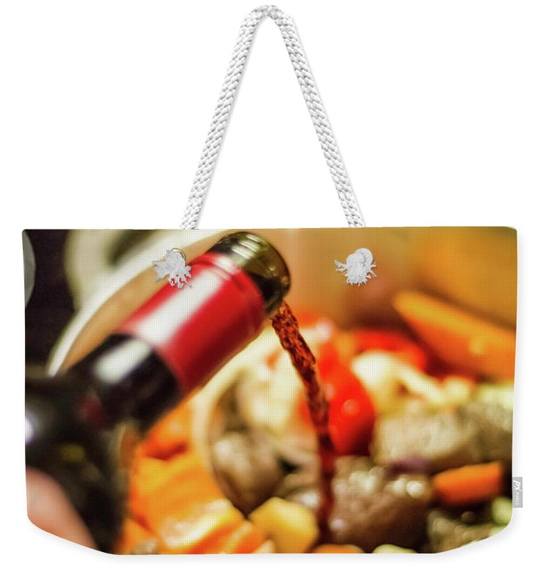 Mature Adult Weekender Tote Bag featuring the photograph Man Pouring Wine Into Vegetables by Manuel Sulzer
