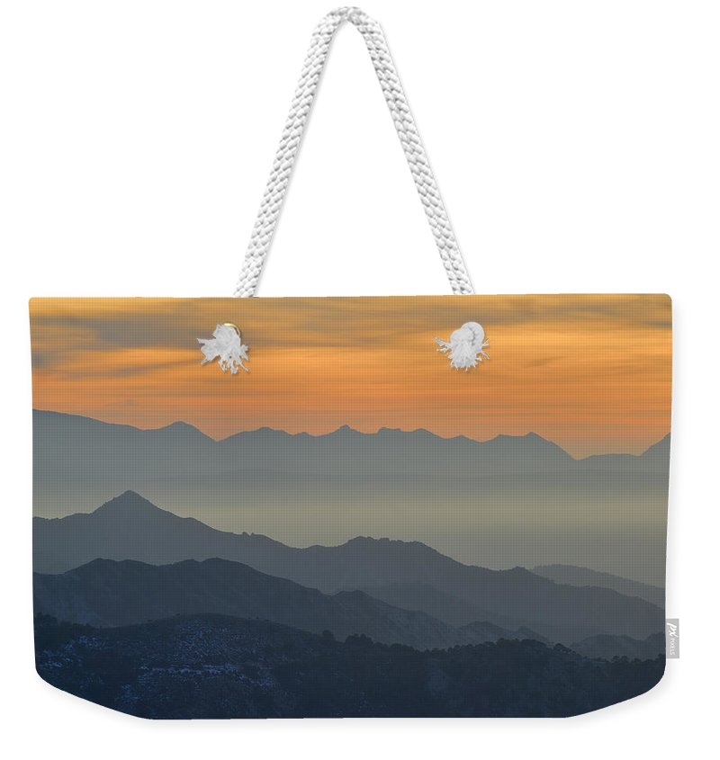 Sunset Weekender Tote Bag featuring the photograph Mists In The Mountains At Sunset by Guido Montanes Castillo