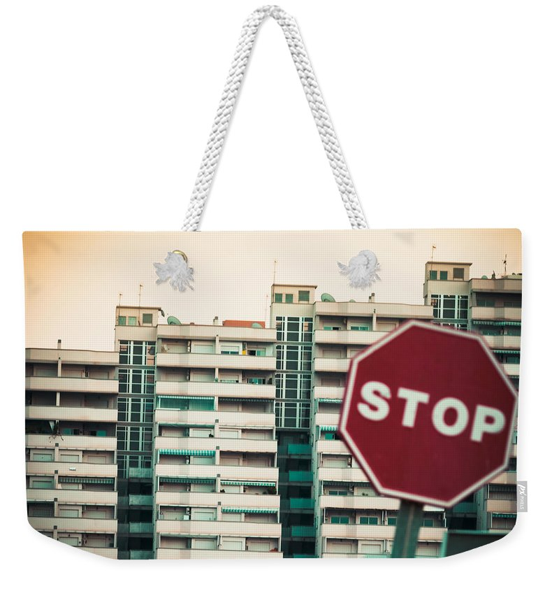 Against Weekender Tote Bag featuring the photograph Mobile Photography Toned Stop Sign And Condo Units by Stephan Pietzko