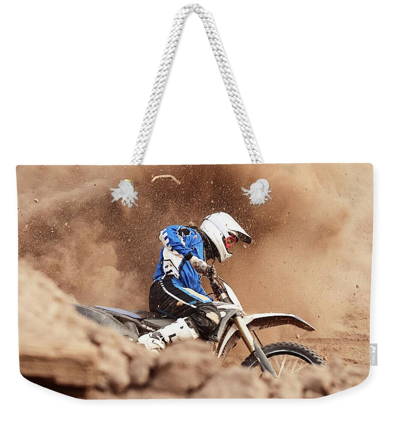 Crash Helmet Weekender Tote Bag featuring the photograph Motocross Biker Taking A Turn In The by Daniel Milchev