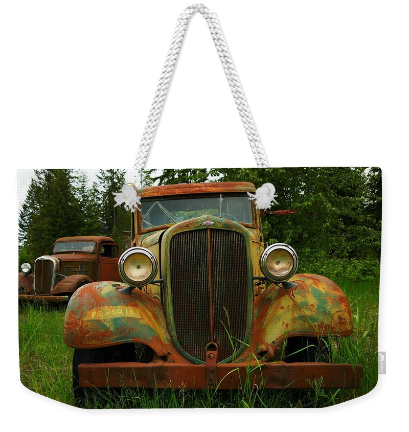 Cars Weekender Tote Bag featuring the photograph Old Cars Left To Decorate The Weeds by Jeff Swan