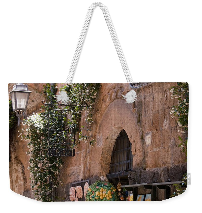 Orvieto Italy Building Buildings Structure Structures Shop Shops Gift Gifts Store Stores Night Light Arch Arches Stone Stones Apartment Apartments City Cities Cityscape Cityscapes Architecture Market Markets Weekender Tote Bag featuring the photograph Old City Shop by Bob Phillips