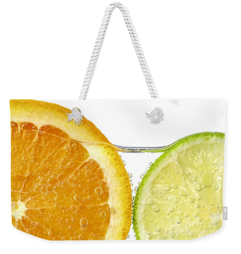 Orange Weekender Tote Bag featuring the photograph Orange And Lime Slices In Water by Elena Elisseeva