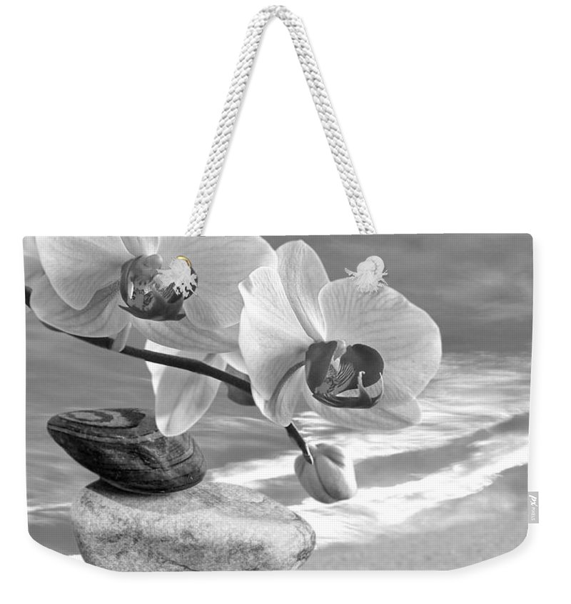 Pebbles Weekender Tote Bag featuring the photograph Orchids And Pebbles On The Sand In Black And White by Gill Billington