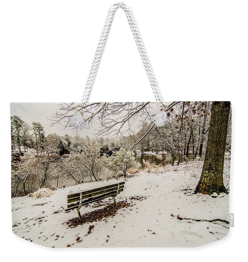 Park Weekender Tote Bag featuring the photograph Park Bench In The Snow Covered Park Overlooking Lake by Alex Grichenko