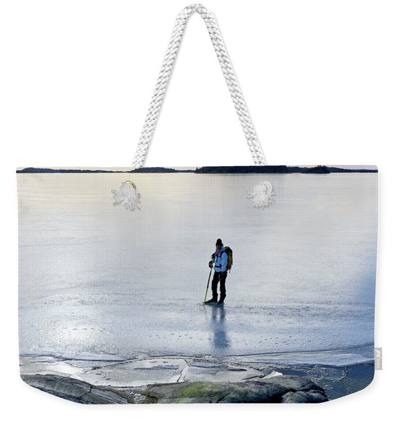 Archipelago Weekender Tote Bag featuring the photograph Person Skating At Frozen Sea by Johner Images