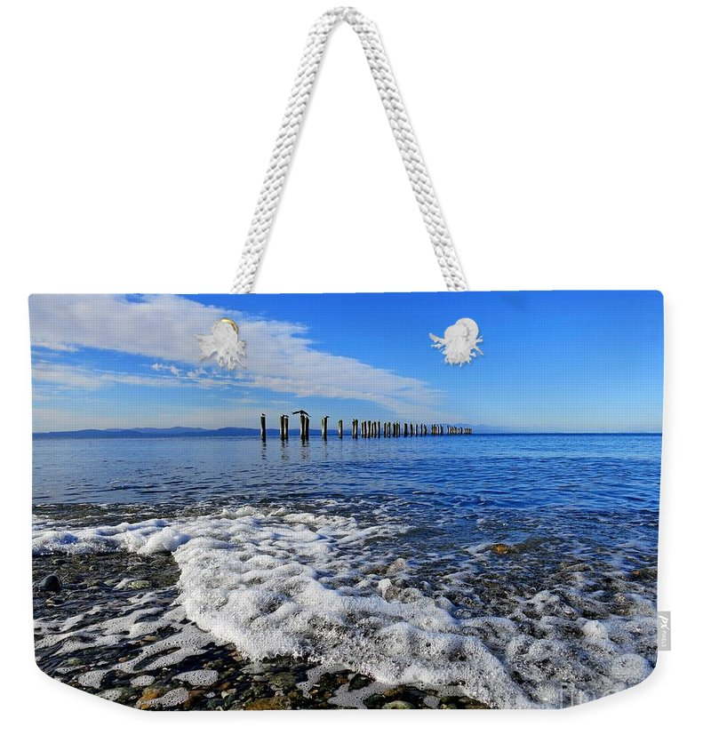 Beach Weekender Tote Bag featuring the photograph Pilings In The Ocean by Lena Photo Art