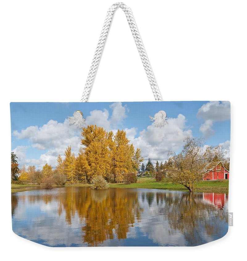 Agricultural Activity Weekender Tote Bag featuring the photograph Red Barn And Fall Colors Reflected In A Pond by Jeff Goulden