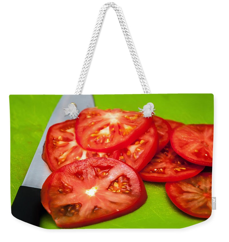 White Weekender Tote Bag featuring the photograph Red Tomato Slices And Knife On Green Chopping Board by Alex Grichenko