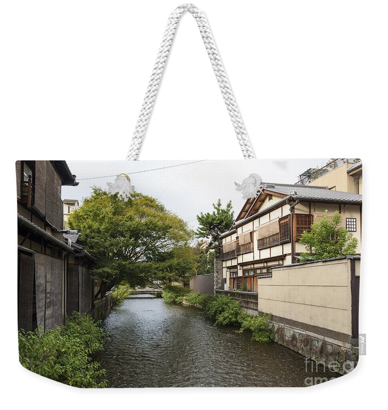 Architecture Weekender Tote Bag featuring the photograph River And Houses In Kyoto Japan by Jacek Malipan