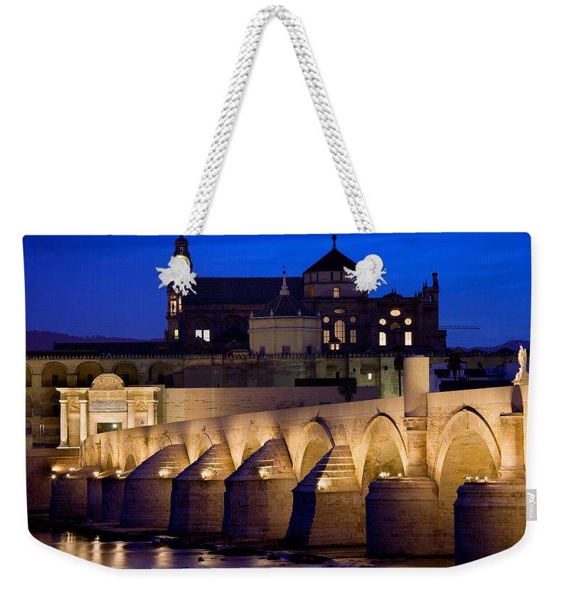 Cordoba Weekender Tote Bag featuring the photograph Roman Bridge And Mezquita In Cordoba At Dawn by Artur Bogacki