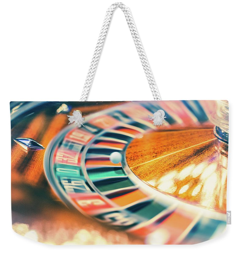 Risk Weekender Tote Bag featuring the photograph Roulette Wheel In Motion by Deimagine