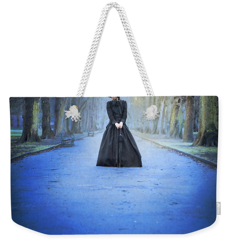 Victorian Weekender Tote Bag featuring the photograph Sad Victorian Woman Alone In A Park At Dusk by Lee Avison