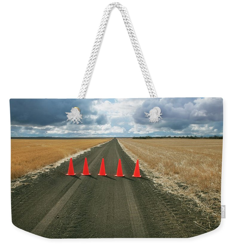 Orange Color Weekender Tote Bag featuring the photograph Safety Cones Lined Up Across A Rural by Benjamin Rondel / Design Pics