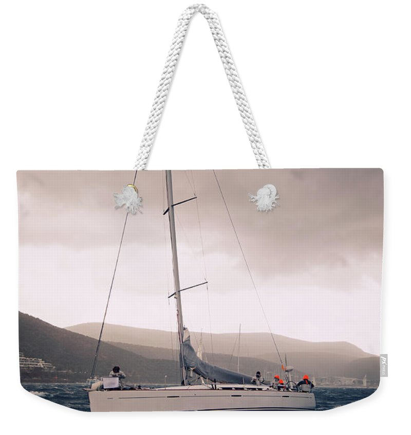 Recreational Pursuit Weekender Tote Bag featuring the photograph Sailing And Stormy Weather by Travenian
