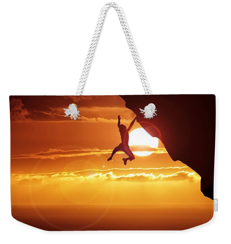 Tranquility Weekender Tote Bag featuring the photograph Silhouette Man Hanging On Cliff Against by Stijn Dijkstra / Eyeem