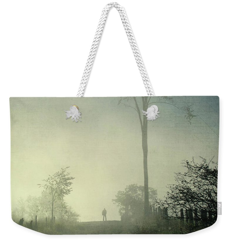 Tranquility Weekender Tote Bag featuring the photograph Silhouette Of A Man In Fog by Francois Dion