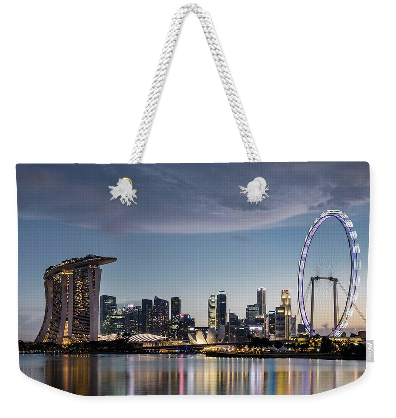 Built Structure Weekender Tote Bag featuring the photograph Singapore Skyline At Dusk by Martin Puddy