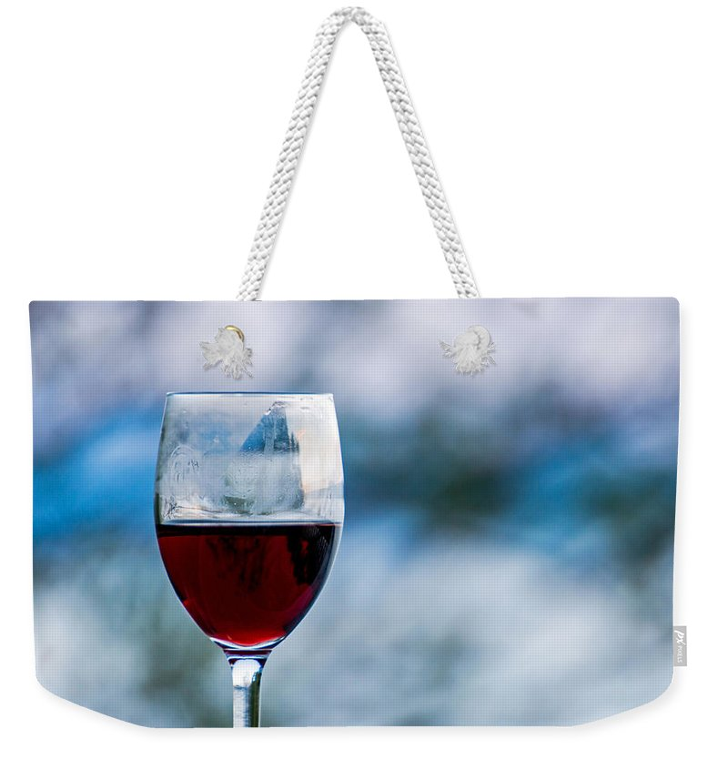 Red Weekender Tote Bag featuring the photograph Single Glass Of Red Wine On Blue And White Background by Photographic Arts And Design Studio
