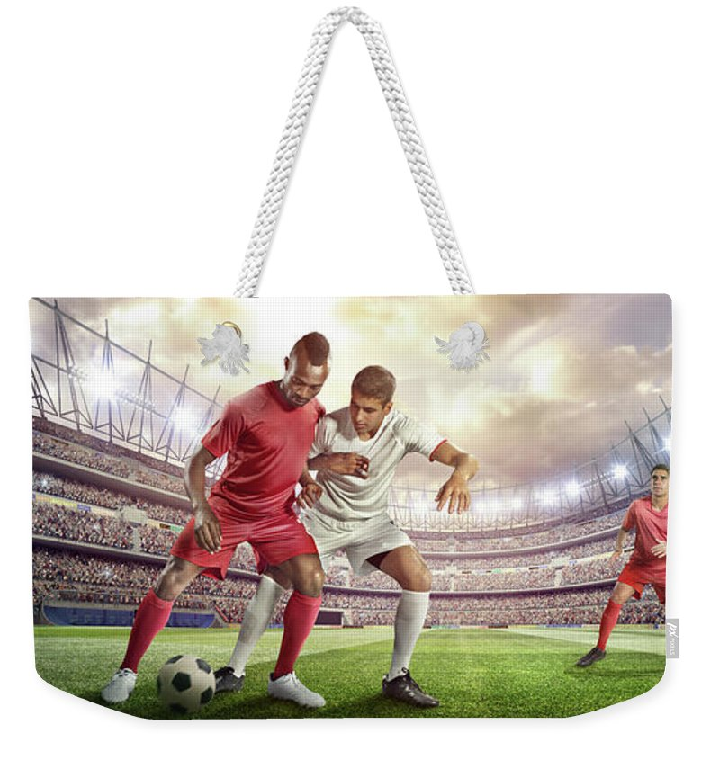 Soccer Uniform Weekender Tote Bag featuring the photograph Soccer Player Tackling Ball In Stadium by Dmytro Aksonov