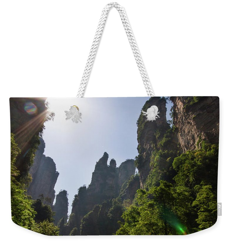 Scenics Weekender Tote Bag featuring the photograph Sun Flare In Zhangjiajie Canyon by Universal Stopping Point Photography