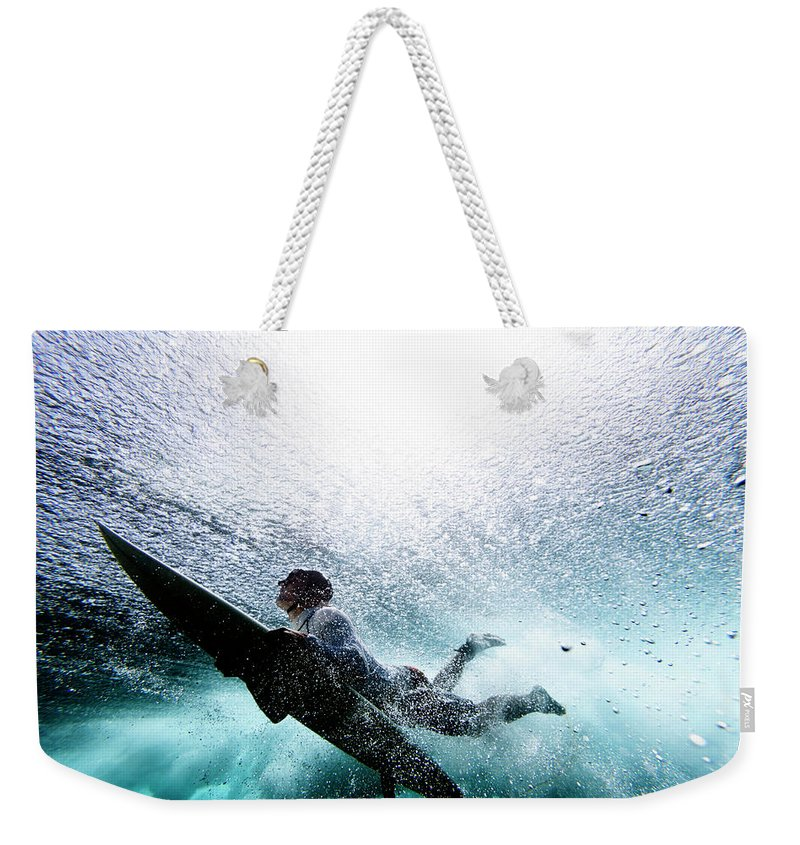 Expertise Weekender Tote Bag featuring the photograph Surfer Duck Diving by Subman