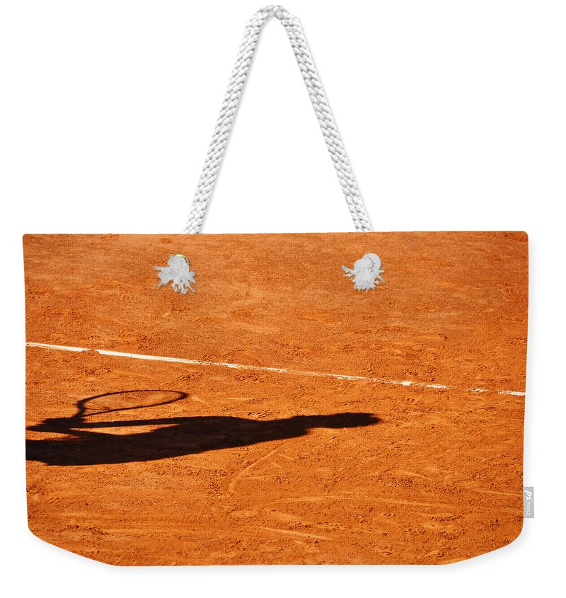 Clay Weekender Tote Bag featuring the photograph Tennis Player Shadow On A Clay Tennis Court by Dutourdumonde Photography