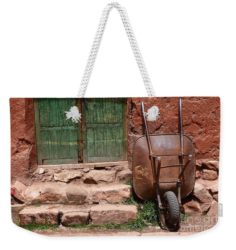 Wheelbarrow Weekender Tote Bag featuring the photograph Rusty Wheelbarrow And Green Door by James Brunker