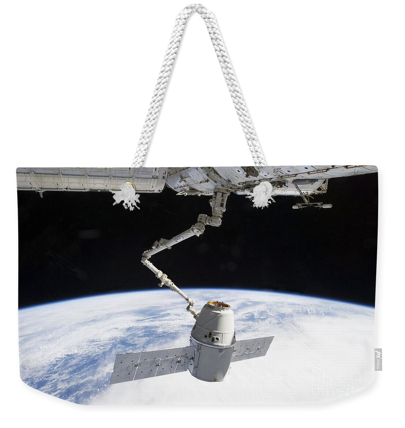 Outer Space Weekender Tote Bag featuring the photograph The Docking Of Spacex Dragon by Stocktrek Images