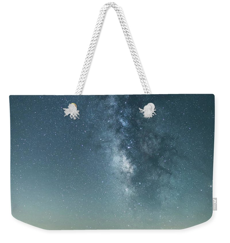 Scenics Weekender Tote Bag featuring the photograph The Milky Way Hovering Above A Town by Trevor Williams