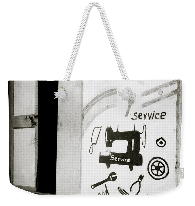 Kitsch Weekender Tote Bag featuring the photograph The Trader by Shaun Higson