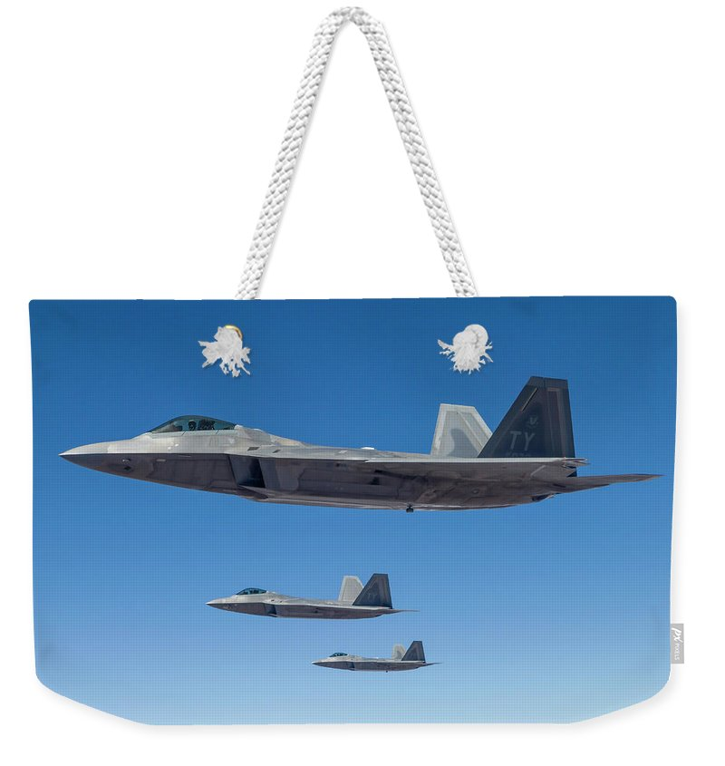 Formation Flying Weekender Tote Bag featuring the photograph Three U.s. Air Force F-22 Raptors by Rob Edgcumbe/stocktrek Images