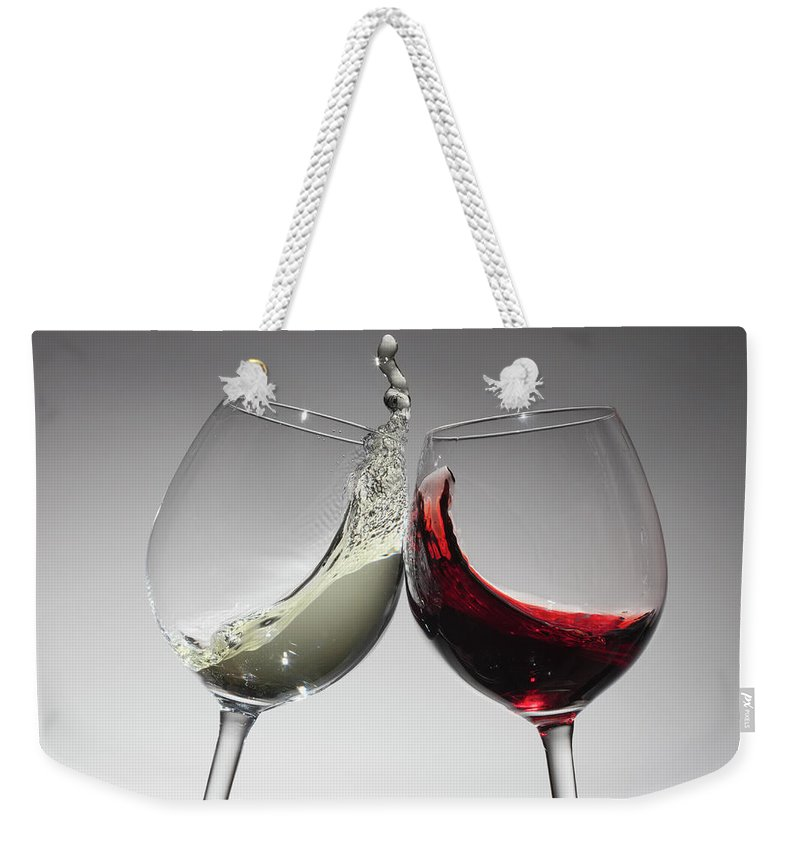 Alcohol Weekender Tote Bag featuring the photograph Toasting With Glasses Of Water And Red by Dual Dual